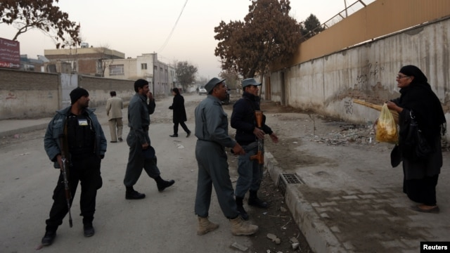 A woman talks to Afghan policemen to allow her to pass as they stand guard near the site of a suicide attack that wounded Afghanistan's spy chief in Kabul, Dec. 6, 2012.