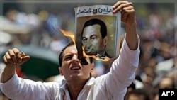 Чоловік спалює фотографію екс-президента Госні Мубарака.