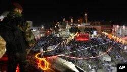 Офицер сил безопасности Палестинской автономии наблюдает за праздничными торжествами на площади Мангер, Вифлеем. 24 декабря 2012 года