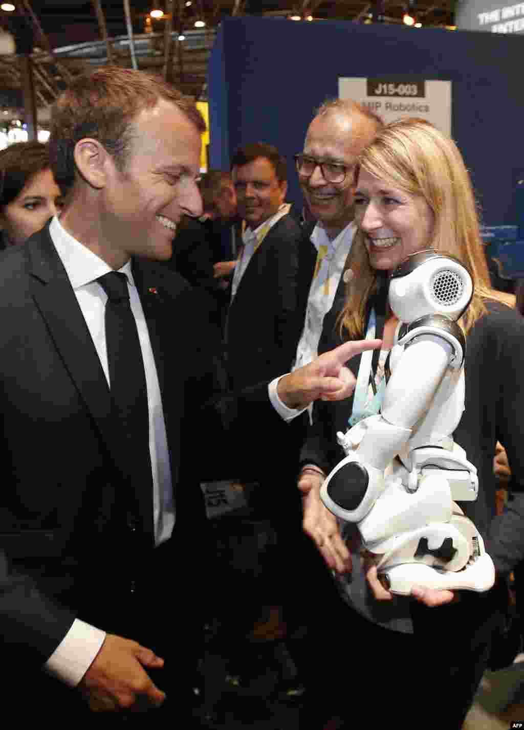 خوش و بش کردن امانوئل ماکرون، رئیس جمهوری فرانسه با این ربات در نمایشگاه آخرین دستاوردهای تکنولوژی در پاریس