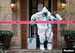 A member of the CG Environmental HazMat team disinfects the entrance to the residence of a health worker at the Texas Health Presbyterian Hospital who has contracted Ebola in Dallas, Texas, Oct.12, 2014.