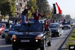 Hundreds of Syrians wave national flags and chant slogans against U.S. President Trump, April 14, 2018, following a wave of U.S., British and French military strikes to punish President Bashar Assad for suspected chemical attack against civilians.