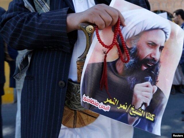 FILE - A Shi'ite protester carries a poster of Sheikh Nimr al-Nimr during a demonstration outside the Saudi embassy in Sanaa, Oct. 18, 2014.