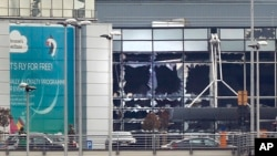 FILE - Broken windows are seen at the scene of explosions at the Brussels airport, Belgium, March 22, 2016.