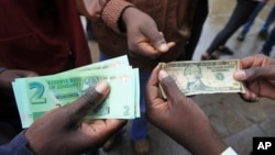 FILE: Zimbabweans compare the new note with the U.S. dollar note following the introduction of new notes by the Reserve Bank of Zimbabwe in Harare, Nov, 28, 2016. (AP Photo/Tsvangirayi Mukwazhi)