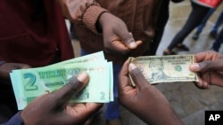FILE: Zimbabweans compare the new note with the U.S. dollar note following the introduction of new notes by the Reserve Bank of Zimbabwe in Harare, Nov, 28, 2016.