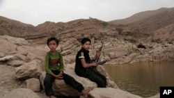 "In this July 30, 2018, photo, a 17-year-old boy holds his weapon in High dam in Marib, Yemen. Experts say child soldiers are ""the firewood"" in the inferno of Yemen's civil war, trained to fight, kill and die on the front lines."
