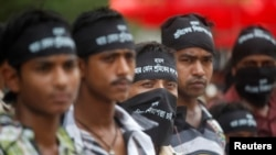 Garment workers wear headbands and cover their faces as they take part in a protest to demand capital punishment for those responsible for the collapse of the Rana Plaza building in Savar, May 1, 2013.