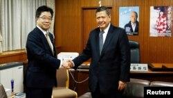 일본을 방문 중인 마르주키 다루스만 유엔 북한인권특별보고관(오른쪽)이 18일 도쿄에서 가토 가쓰노부 납치문제 담당상과 만나 악수하고 있다.