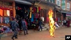 13일 네팔 카트만두에서 티베트 승려가 분신을 시도한 가운데, 불을 끄기 위해 모여든 경찰들. 이 승려는 병원으로 옮겨졌지만 위독한 상황이다.