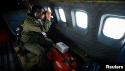 Salah seorang tentara AU Malaysia menggunakan teropong di atas pesawat CN235 saat melakukan operasi pencarian pesawat di atas Selat Malaka (12/3).