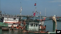 Cambodian workers use barrels to float a fishing boat which just hauled from the Gulf of Thailand.
