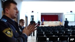 FILE - Security workers do a last inspection of the War Crimes Court room before the inauguration ceremony of the Bosnian War Crimes Court, in Sarajevo, March 9, 2005.