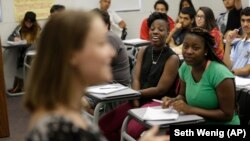 Students listen to their teacher during an English class at an Upward Bound program that serves as a pathway to college for students from low-income families, in New York.