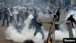 FILE - An anti-government protester throws a teargas canister back at police during riots at Altamira square in Caracas, Venezuela, March 6, 2014.