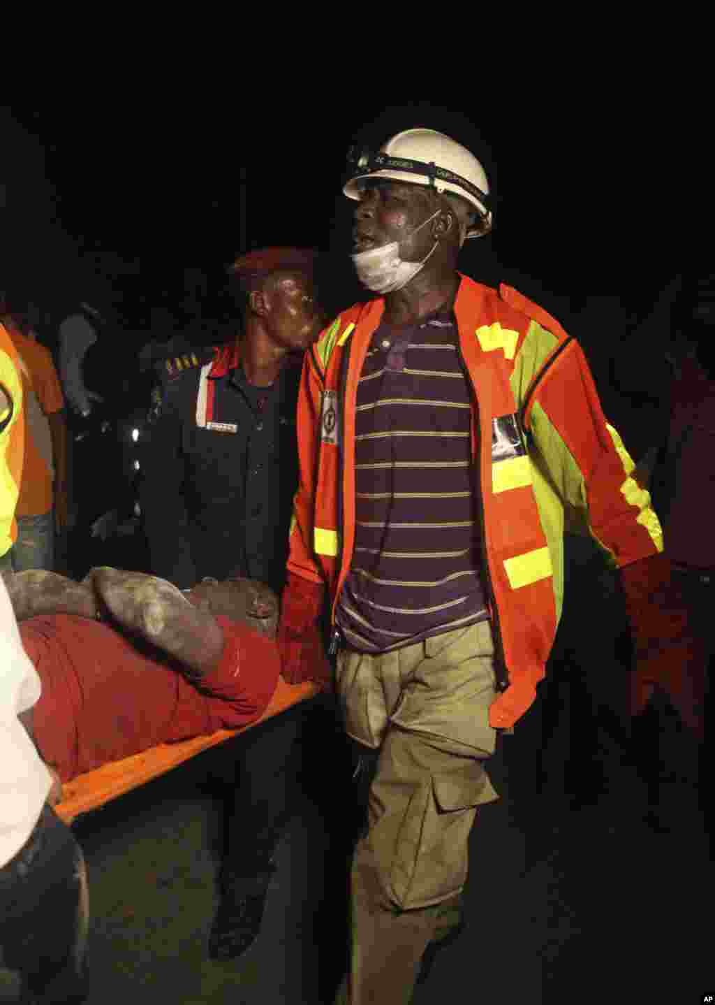 Rescue workers carry a survivor from the rubble of a building under construction which collapsed in Lagos, Nigeria, Nov, 4. 2013.