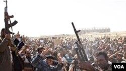 Kelompok bersenjata Libya anti-Moammar Gaddafi melepas tembakan ke udara dalam acara pemakaman massal pemberontak yang tewas dalam pertempuran di Ajdabiya, Kamis (3/3).