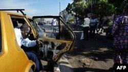 Un client descend d'un taxi collectif sur une artère principale de Kinshasa, le 09 octobre 2004