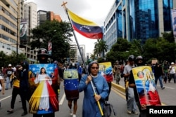 A nun carries Venezuelan flag next to demonstrators carrying homemade shields with religious images, during a rally against Venezuelan President Nicolas Maduro's government in Caracas, Venezuela, June 7, 2017