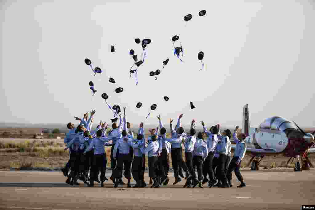 Israeli Air Force cadets toss their caps during their graduation ceremony at Hatzerim air base in southern Israel.