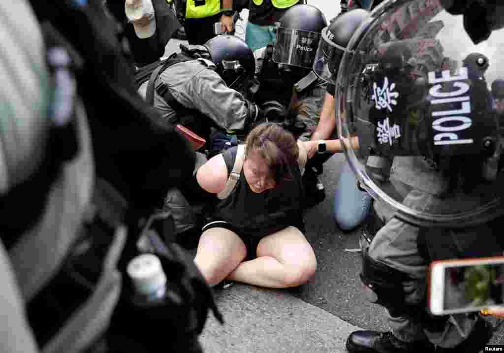 """Manifestantes aseguran que luchan contra lo que consideran la erosión del acuerdo conocido como """"un país, dos sistemas"""" que sobre el papel garantizaba una cierta autonomía de Hong Kong desde que China retomara la isla del control británico en 1997. En la foto, agentes de la policía antidisturbios detienen a un manifestante contra el proyecto de ley de extradición durante una marcha en el barrio de Sham Shui Po en Hong Kong, China, el 11 de agosto de 2019."""