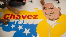 Supporters of Venezuela's President Hugo Chavez create a poster with his image alongside an outline of their country in Caracas, December 14, 2012.
