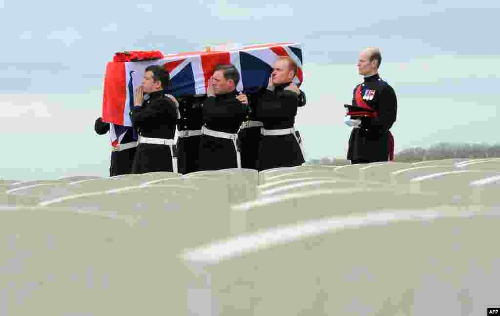 A coffin containing the remains of a British soldier is carried in the Honorable Artillery Company Cemetery at Ecoust-Saint- Mein as four British soldiers were laid to rest with full military honors in northern France, nearly a century a century after they were killed in action in World War I. Their bodies were discovered in 2009 when a local farmer was clearing one of his fields.