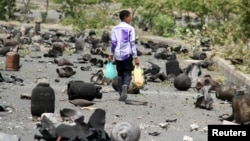 FILE - A boy walks on a street littered with cooking gas cylinders after a fire and explosions destroyed a nearby gas storage during clashes between fighters of the Popular Resistance Committees and Houthi fighters, in Yemen's southwestern city of Taiz, July 19, 2015.