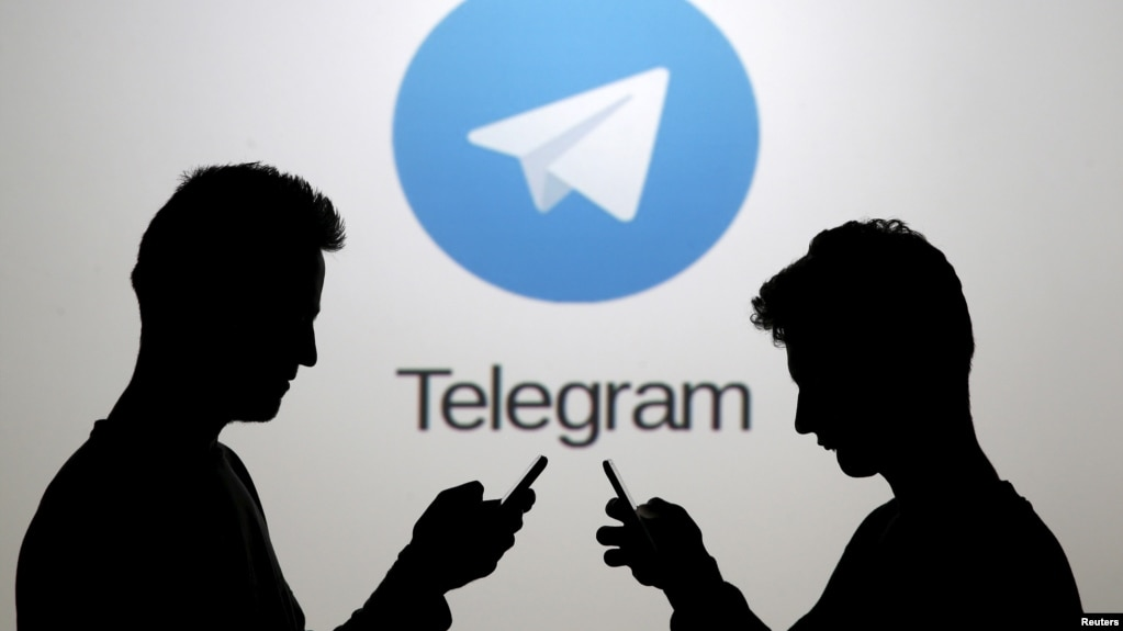 Russia blocks telegram messaging service two men pose with smartphones in front of a screen showing the telegram logo in this stopboris Image collections
