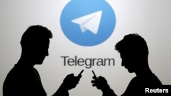 Two men pose with smartphones in front of a screen showing the Telegram logo in this picture illustration taken in Zenica, Bosnia and Herzegovina November 18, 2015. (REUTERS/Dado Ruvic)
