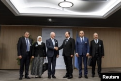 UN Special Envoy for Syria Staffan de Mistura (3rd L) shakes hands with head of the Syrian Negotiation Commission (SNC) Nasr al-Hariri (3rd R) next to opposition delegation members (from L-R) Khaled al-Mahamid, Hanadi Abu Arab, Jamal Suliman and Safwan Akash, on the opening of a new round of Syria's peace talks at the United Naitons Office in Geneva, Switzerland, Nov. 28, 2017.