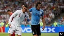 Cristiano Ronaldo, à gauche, aide Edinson Cavani à quitter le terrain après sa blessure, Russie, le 30 juin 2018