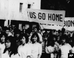 """Teenage schoolgirls carry banners like """"US Go Home"""" and """"Perfidious Albion"""" through the street on March 11, 1964, in Phnom Penh before they sacked the US Embassy there. (AP Photo)"""