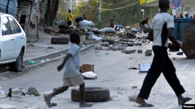 FILE - People walk through a litter-filled street after residents of a camp for people displaced by Haiti's Jan. 2010 earthquake blocked streets after some tents were destroyed, Port-au-Prince, Feb. 15, 2013.