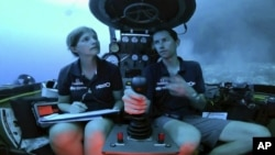 Lucy Woodall, Nekton Mission principle scientist, left, and pilot Randy Holt inside a submersible 60 meters below surface of Indian Ocean during a descent into the Indian Ocean off Alphonse Atoll near the Seychelles, Tuesday March 12, 2019.