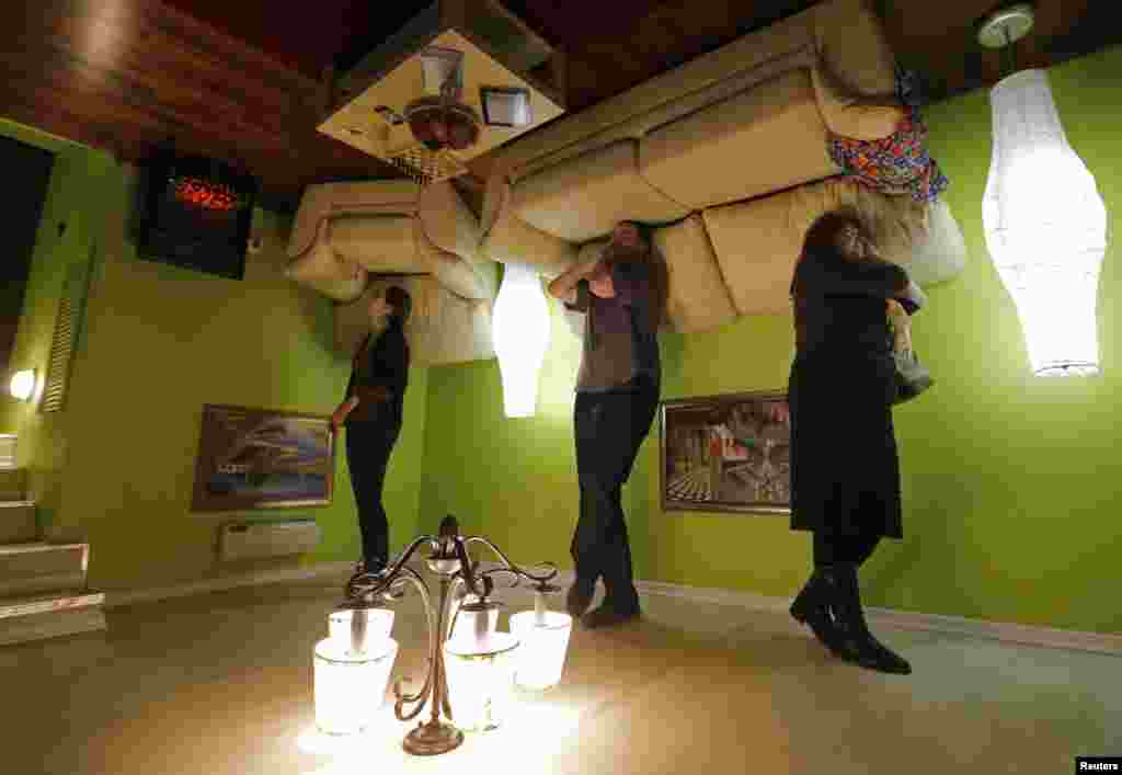"People take a tour in an ""upside down home"" in St. Petersburg, Russia. The exhibition charges less than $10 for a walk through three-room and two-bathroom house."
