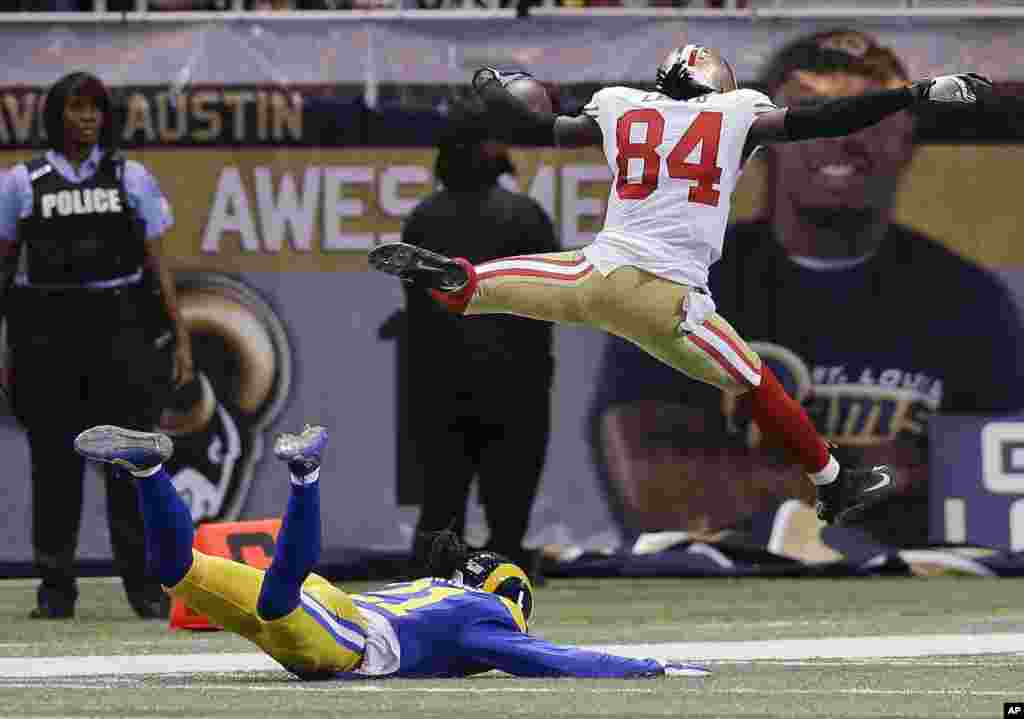 San Francisco 49ers wide receiver Brandon Lloyd (84) jumps into the end zone ahead of St. Louis Rams cornerback Janoris Jenkins (21) as Lloyd scores a touchdown on an 80-yard pass play in the second quarter of an NFL football game in St Louis, Missouri, USA, Oct. 13, 2014.