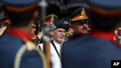 FILE - Afghan President Ashraf Ghani (C) inspects an honor guard during the Independence Day celebrations in Kabul, Afghanistan, Aug 18, 2016. The peace deal with Hekmatyar's group could provide a boost to the beleaguered Ghani.