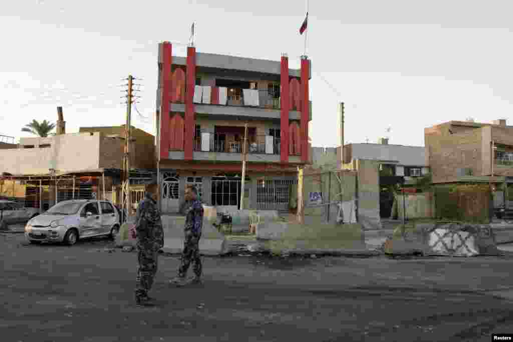 Police inspect the site of an attack that killed at least 18 people and wounded about 50 people when two parked car bombs went off in two mainly Shi'ite districts, in Baghdad's Al-Amil district, Sept. 2, 2014.