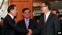 Cambodian Prime Minister Hun Sen, left, shakes hands with opposition party leader Sam Rainsy, right, after a meeting, as Sar Kheng, center, deputy prime minister, looks on at the National Assembly in Phnom Penh, file photo.