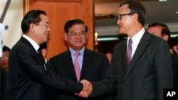 Cambodian Prime Minister Hun Sen, left, shakes hands with opposition party leader Sam Rainsy, right, after a meeting, as Sar Kheng, center, deputy prime minister, looks on at the National Assembly in Phnom Penh, Monday, Sept. 16, 2013.