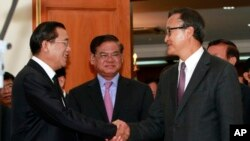 Cambodian Prime Minister Hun Sen, left, shakes hands with opposition party leader Sam Rainsy, right, after a meeting, as Sar Kheng, center, deputy prime minister, looks on at the National Assembly in Phnom Penh, Cambodia, Monday, Sept. 16, 2013.