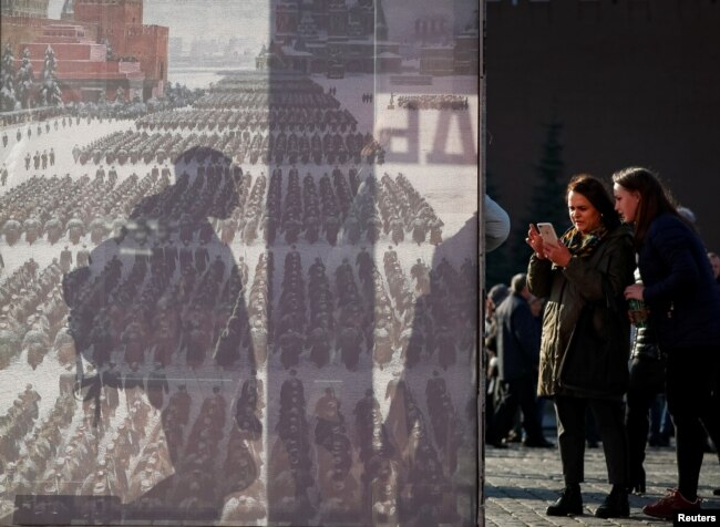FILE - Two women are seen near a display after a military parade in Red Square, Moscow, Russia Nov. 7, 2018.