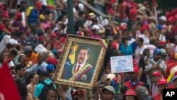 一名委内瑞拉现政府支持者在加拉加斯举行的反帝集会上手举马杜罗画像(2019年3月30日)