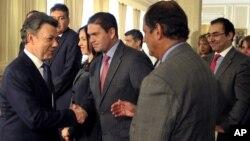 El presidente colombiano Juan Manuel Santos recibe las felicitaciones de su ministro de Defensa, Juan Carlos Pinzón y otros miembros del gabinete, luego de su discurso en el Palacio de Nariño.