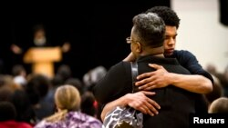 Mourners embrace during the funeral for Tony Robinson Jr. at Madison East High School in Madison, Wisconsin, March 14, 2015.
