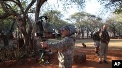 Un chasseur américain Steve Schultz, à gauche, essaie son arc de chasse avant de quitter le camp de Melorani Safaris au Olifantsvallei, en Afrique du Sud, 18 avril 2015