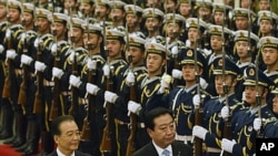 Japanese Prime Minister Yoshihiko Noda, right, and Chinese Premier Wen Jiabao inspect a guard of honor during a welcoming ceremony at Great Hall of the People in Beijing, China, December 25, 2011.