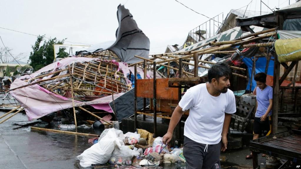 Seorang warga berjalan melewati kios-kios yang rusak di pasar umum ketika Topan Mangkhut berlar di kota Tuguegarao di provinsi Cagayan, Filipina timur laut, 15 September 2018.