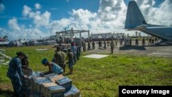 Sailors assigned to the U.S. Navy's forward-deployed aircraft carrier USS George Washington, Marines assigned to the 3 Marine Expeditionary Brigade, and Philippine civilians unload relief supplies in support of Operation Damayan. ((U.S. Navy photo by Mass Communication Specialist Seaman Beverly Lesonik)